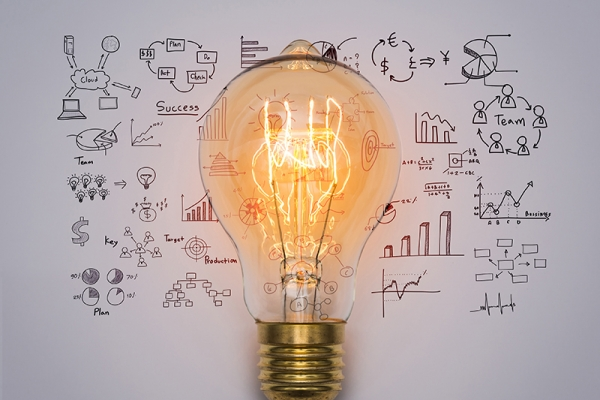 Light bulb on top of business stat sketches