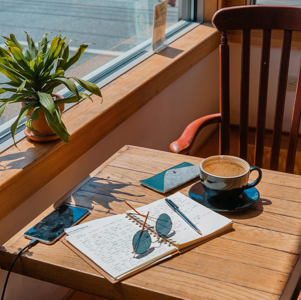 Coffee table at a cafe with a notebook, sunglasses, coffee and a phone that is charging.