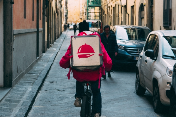 A delivery person riding a bike with a delivery box on their back