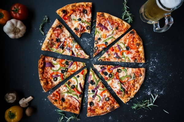 an everything pizza on a black top table
