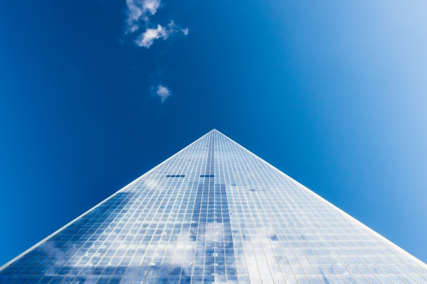 A vertical view of a building upwards towards a blue sky